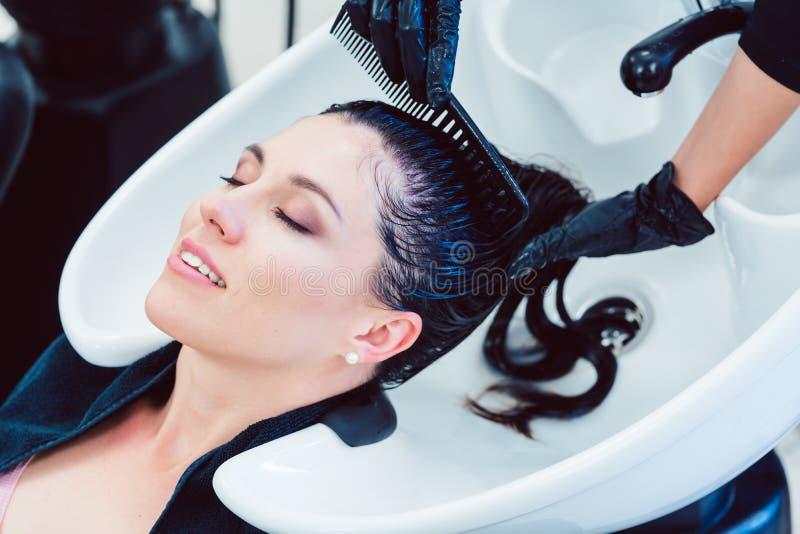 Χειροτεχνική τρίχα πλύσης κομμωτών της γυναίκας πελατών στοκ εικόνες με δικαίωμα ελεύθερης χρήσης