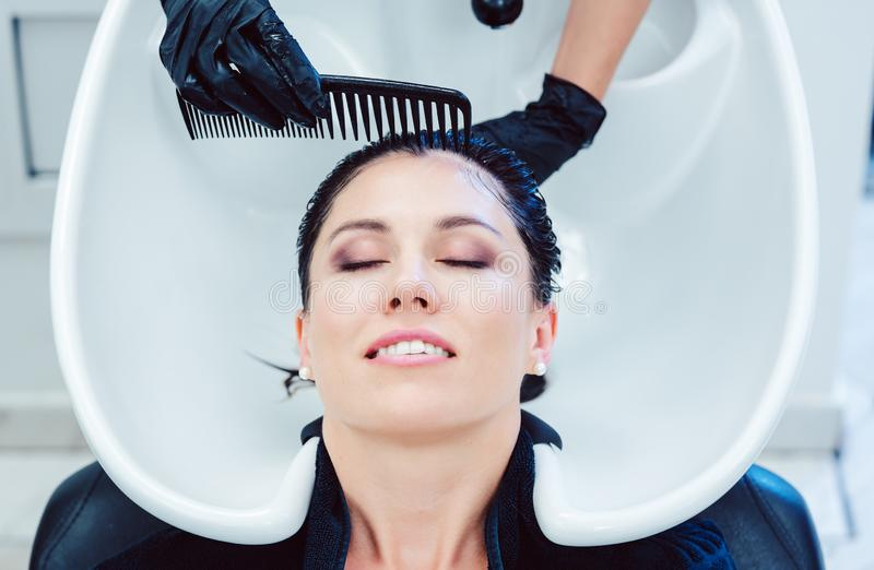 Χειροτεχνική τρίχα πλύσης κομμωτών της γυναίκας πελατών στοκ φωτογραφίες με δικαίωμα ελεύθερης χρήσης