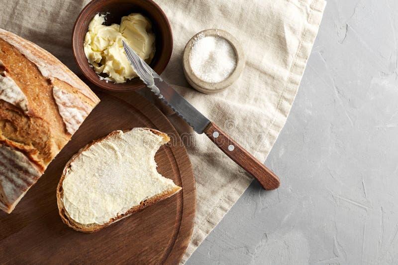 Χειροτεχνικό τεμαχισμένο ψωμί φρυγανιάς με το βούτυρο και ζάχαρη στον ξύλινο τέμνοντα πίνακα Απλό πρόγευμα στο γκρίζο συγκεκριμέν στοκ φωτογραφία με δικαίωμα ελεύθερης χρήσης