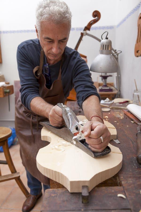 Χειροτεχνικό lutemaker που λειτουργεί ένα βιολί στοκ φωτογραφίες