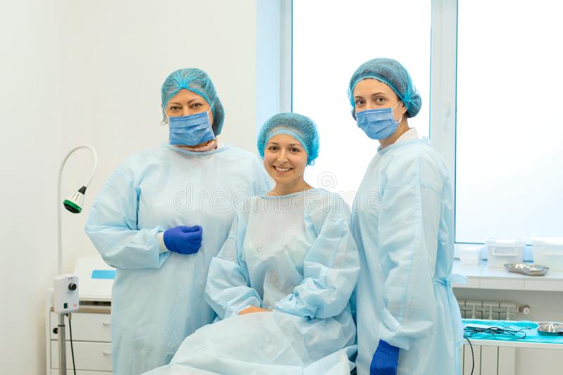 Χειρούργοι και ευτυχής ασθενής μετά από την επιτυχή χειρουργική επέμβαση για να απομακρύνει έναν τυφλοπόντικα στην πλάτη στοκ εικόνες
