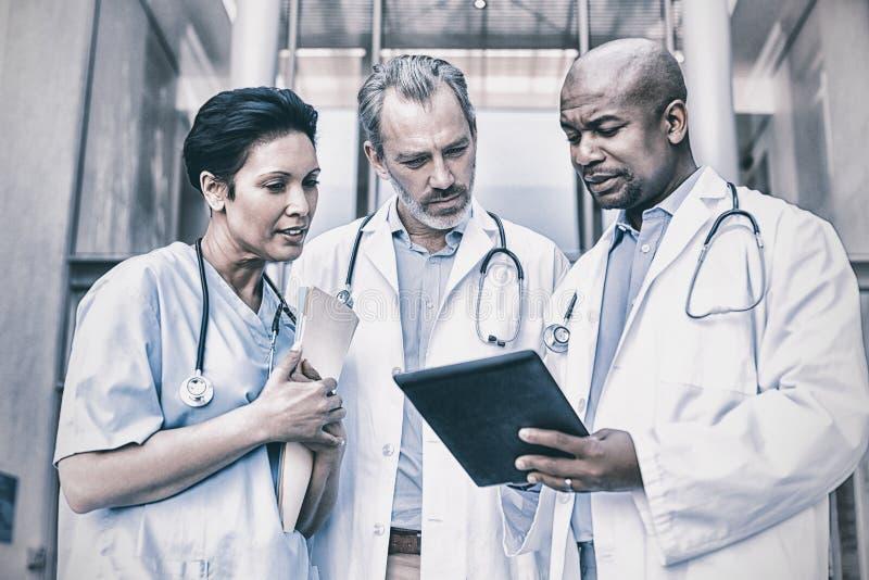 Χειρούργοι και νοσοκόμα που διοργανώνουν τη συζήτηση σχετικά με την ψηφιακή ταμπλέτα στοκ φωτογραφίες