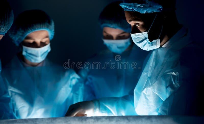 Χειρούργοι που εκτελούν τη χειρουργική λειτουργία στο σκοτεινό λειτουργούν δωμάτιο στοκ φωτογραφία