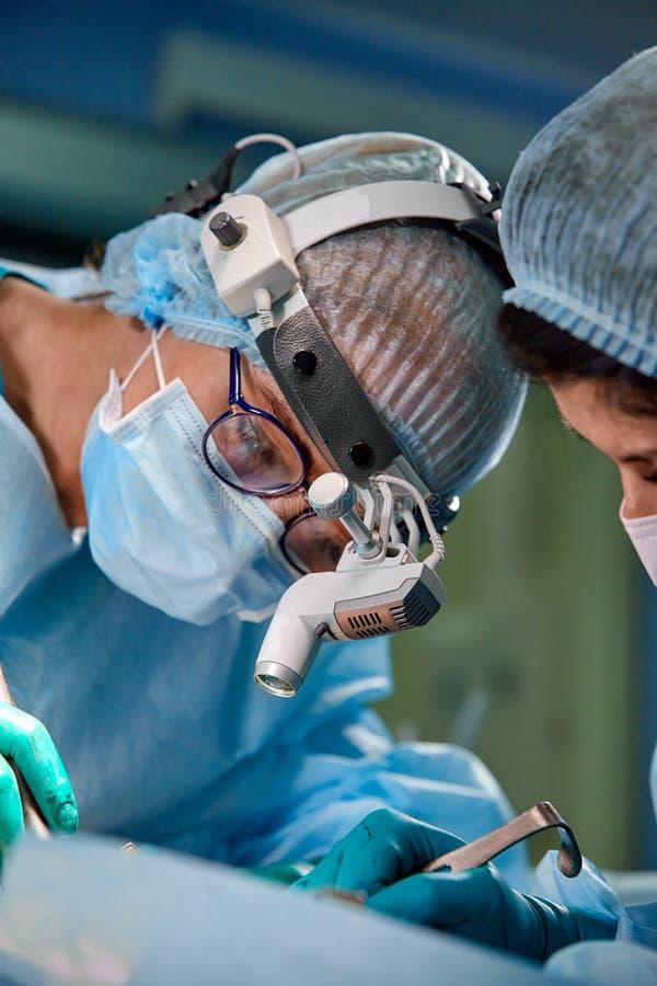 Χειρούργος και ο βοηθός του που εκτελούν τη αισθητική χειρουργική στη μύτη στο λειτουργούν δωμάτιο νοσοκομείων Μύτη που αναδιαμορ στοκ φωτογραφίες με δικαίωμα ελεύθερης χρήσης