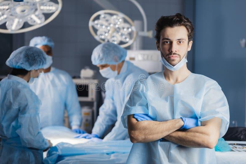 Χειρούργος που εξετάζει τη κάμερα με τους συναδέλφους στοκ φωτογραφίες με δικαίωμα ελεύθερης χρήσης