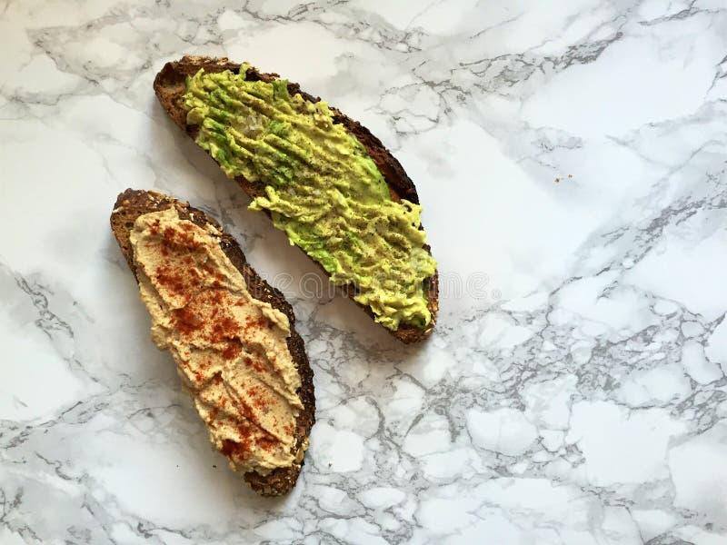 Χειρωνακτική ολόκληρη φρυγανιά σιταριού με το καταπληκτικά αβοκάντο και το hummus στοκ εικόνα με δικαίωμα ελεύθερης χρήσης