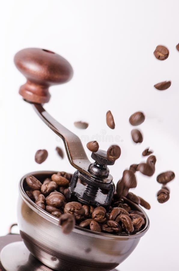 Χειρωνακτικός μύλος καφέ με τα φασόλια καφέ Άσπρη ανασκόπηση Σύγχρονο ύφος καφές φασολιών που ψήνεται Φασόλια καφέ μετεωρισμού στοκ φωτογραφία με δικαίωμα ελεύθερης χρήσης