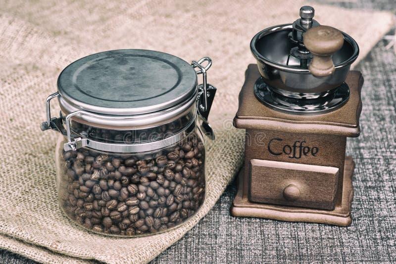 Χειρωνακτικός μύλος καφέ με τα φασόλια καφέ στοκ εικόνα