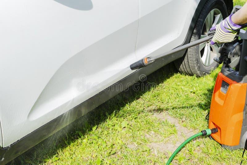Χειρωνακτικό πλύσιμο αυτοκινήτων με το διατηρημένο σταθερή ατμοσφαιρική πίεση νερό στο πλύσιμο αυτοκινήτων έξω Πλύση θερινών αυτο στοκ εικόνα με δικαίωμα ελεύθερης χρήσης