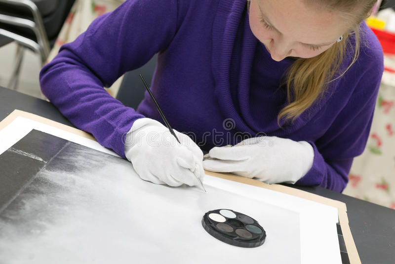 Χειρωνακτικό ρετουσάρισμα τυπωμένων υλών φωτογραφιών από τη γυναίκα με το μελάνι βουρτσών και χρωστικών ουσιών στοκ εικόνες με δικαίωμα ελεύθερης χρήσης
