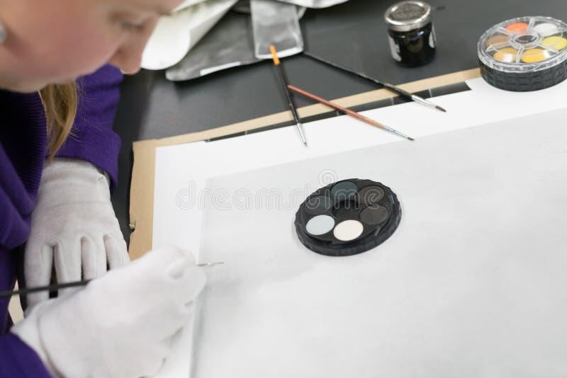 Χειρωνακτικό ρετουσάρισμα τυπωμένων υλών φωτογραφιών από τη γυναίκα με το μελάνι βουρτσών και χρωστικών ουσιών στοκ φωτογραφίες με δικαίωμα ελεύθερης χρήσης