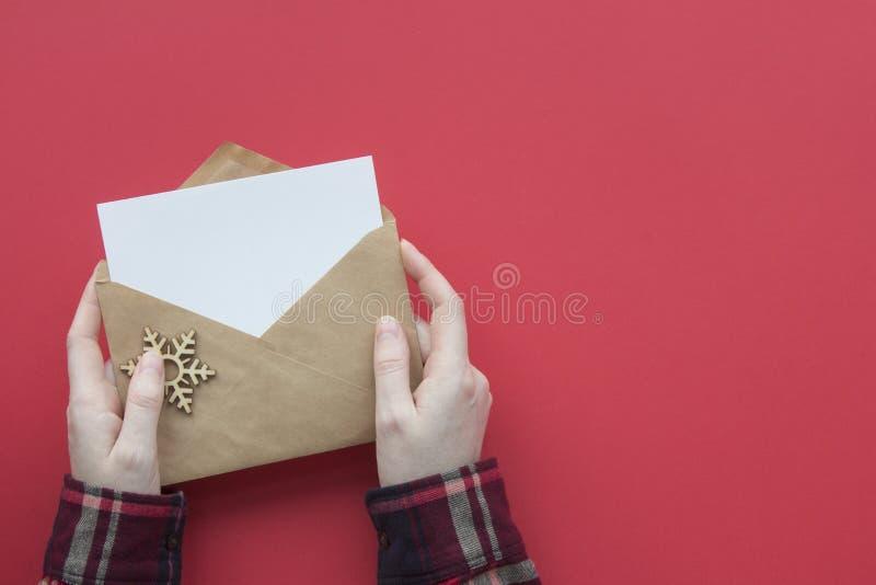 Χειρός με θήκη πουκάμισο στο κόκκινο φόντο Κορυφαία εμφάνιση χριστουγεννιάτικης κάρτας στοκ εικόνα
