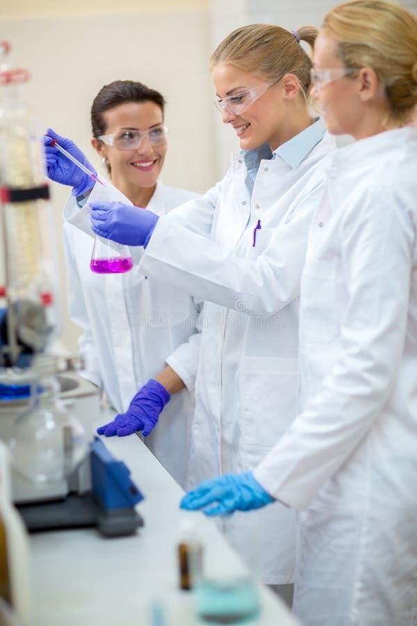Χημικοί βοηθοί που παίρνουν το δείγμα από τη φιάλη στοκ εικόνα