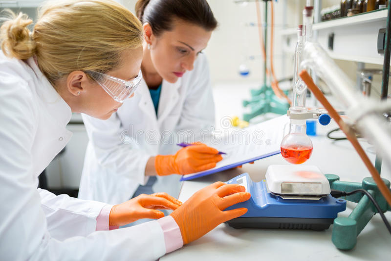 Χημικοί τεχνικοί που εργάζονται στο πείραμα στο εργαστήριο στοκ εικόνα