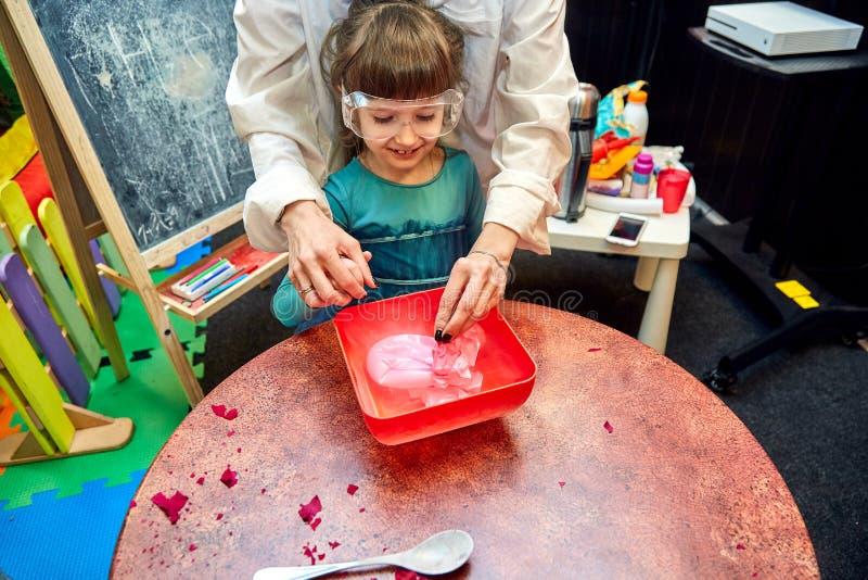 Χημικός παρουσιάστε για τα παιδιά Ο καθηγητής πραγματοποίησε τα χημικ στοκ εικόνα
