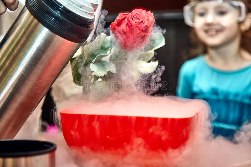 Χημικός παρουσιάστε για τα παιδιά Ο καθηγητής πραγματοποίησε τα χημικ στοκ φωτογραφία