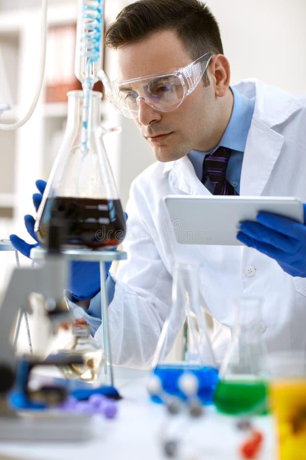 Χημικό πείραμα ανάλυσης επιστημόνων με την ταμπλέτα στοκ φωτογραφία με δικαίωμα ελεύθερης χρήσης