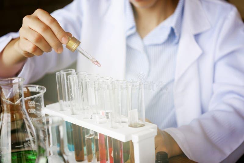 χημικό υγρό πτώσης χεριών επιστημόνων στο σωλήνα στοκ εικόνες