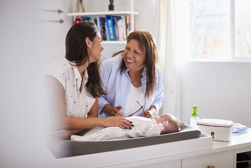 Χιλιετές ισπανικό παιχνίδι μητέρων και γιαγιάδων με το γιο μωρών στο μεταβαλλόμενο πίνακα, εκλεκτική εστίαση στοκ φωτογραφία με δικαίωμα ελεύθερης χρήσης
