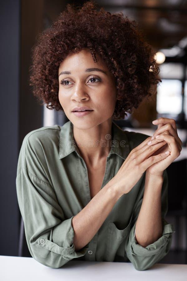 Χιλιετής μαύρος θηλυκός δημιουργικός σε ένα γραφείο που κοιτάζει μακριά στο σχέδιο, κλείνει επάνω στοκ φωτογραφία με δικαίωμα ελεύθερης χρήσης