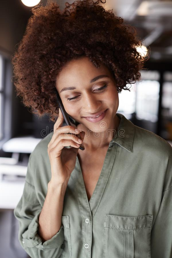 Χιλιετής μαύρος θηλυκός δημιουργικός σε ένα γραφείο που χρησιμοποιεί το smartphone, που κοιτάζει κάτω, κλείνει επάνω, κάθετος στοκ φωτογραφίες