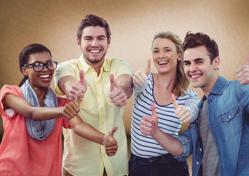 Χιλιετής ομάδα που δίνει τους αντίχειρες επάνω στο καφετί κλίμα στοκ φωτογραφίες με δικαίωμα ελεύθερης χρήσης