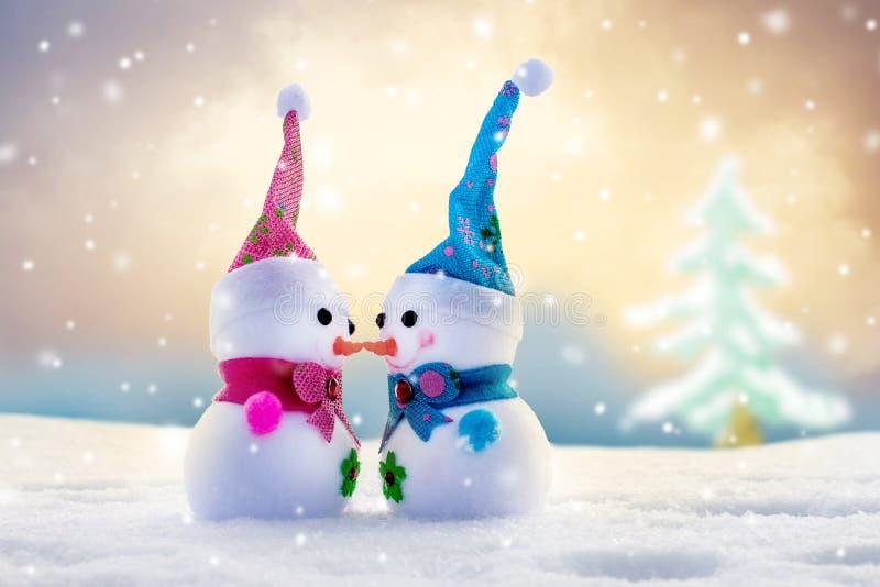 Χιονάνθρωποι παιχνιδιών σε ένα φωτεινό, ζωηρόχρωμο χειμερινό υπόβαθρο Δύο είναι ερωτευμένα Συγχαρητήρια σε Day_ του βαλεντίνου στοκ εικόνες