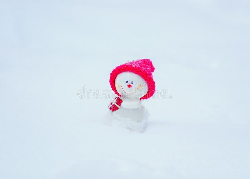 χιονάνθρωπος παιχνιδιών σε μια φωτεινή ρόδινη συνεδρίαση ΚΑΠ άσπρο snowdrift με ένα δώρο στοκ φωτογραφία