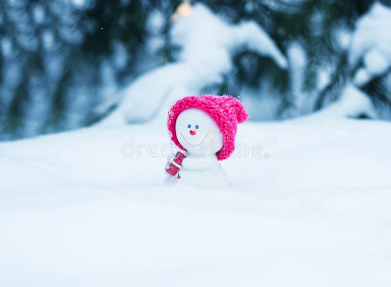 χιονάνθρωπος παιχνιδιών σε μια φωτεινή ρόδινη συνεδρίαση ΚΑΠ άσπρο snowdrift με ένα δώρο στοκ φωτογραφίες με δικαίωμα ελεύθερης χρήσης