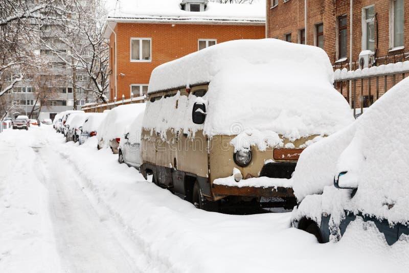 Χιονισμένα αυτοκίνητα σε έναν χώρο στάθμευσης που χτίζει πλησίον στοκ φωτογραφία με δικαίωμα ελεύθερης χρήσης