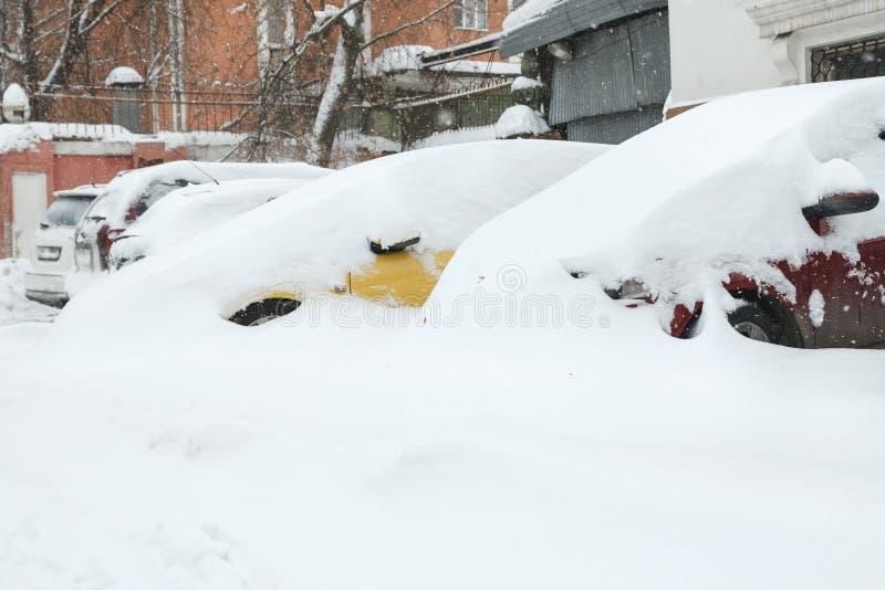 Χιονισμένα αυτοκίνητα σε έναν χώρο στάθμευσης που χτίζει πλησίον στοκ εικόνα με δικαίωμα ελεύθερης χρήσης