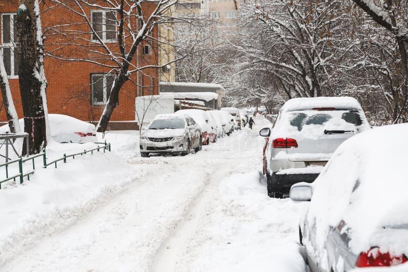 Χιονισμένα αυτοκίνητα σε έναν χώρο στάθμευσης που χτίζει πλησίον στοκ εικόνα