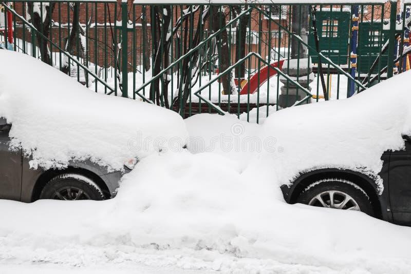 Χιονισμένα αυτοκίνητα σε έναν χώρο στάθμευσης που χτίζει πλησίον στοκ φωτογραφίες με δικαίωμα ελεύθερης χρήσης
