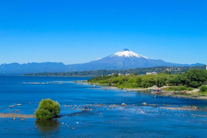 Χιονισμένη σύνοδος κορυφής ηφαιστείων ύψους επάνω από τη λίμνη στοκ εικόνα