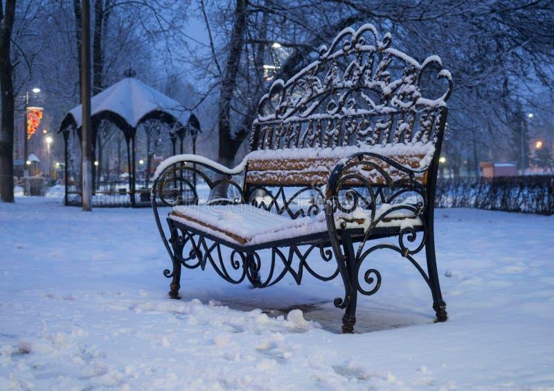 Χιονισμένος πάγκος στο πάρκο πόλεων με τη συμφιλίωση πάγκων επιγραφής στοκ εικόνες
