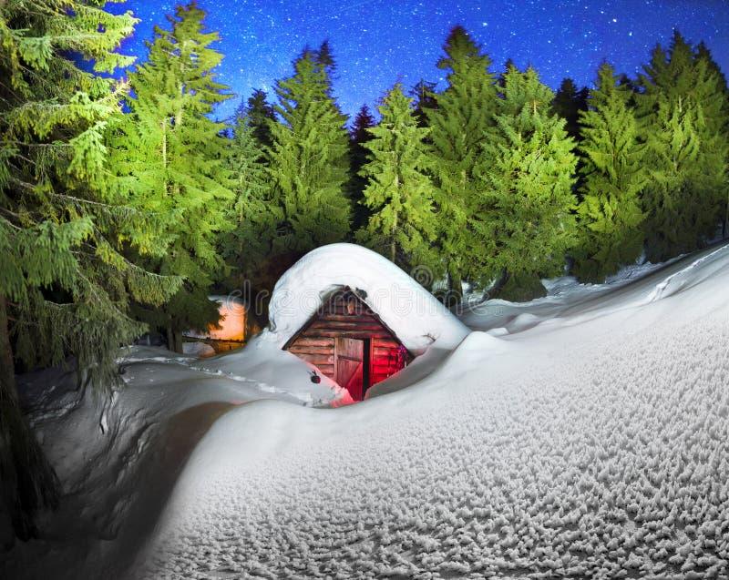 Χιονισμένο σπίτι παραμυθιού στα βουνά στοκ εικόνες