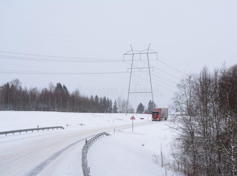 Χιονοπτώσεις στην εθνική οδό Μακριά πλησιάζοντας πόλος δύναμης φορτηγών και υψηλής τάσης στοκ φωτογραφία με δικαίωμα ελεύθερης χρήσης