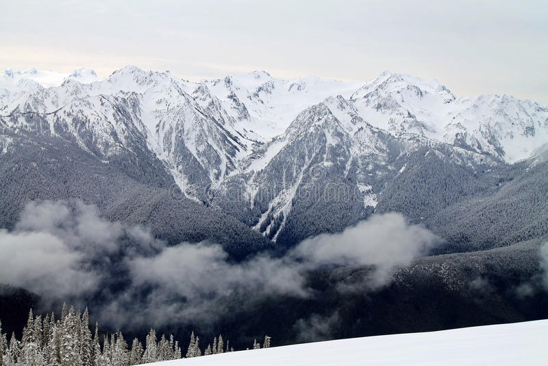 Χιονοσκεπής σειρά βουνών πέρα από έναν χιονώδη τομέα στοκ εικόνες