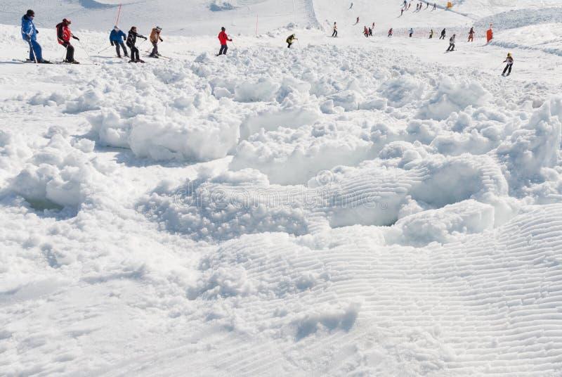 Χιονοστιβάδα κλίσεων σκι που καλύπτεται με τους σκιέρ στοκ εικόνες