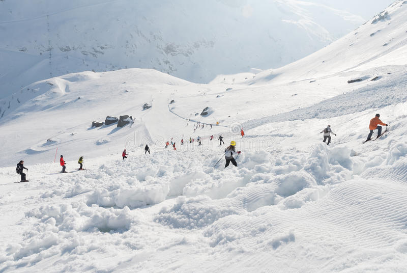 Χιονοστιβάδα κλίσεων σκι που καλύπτεται με τους σκιέρ στοκ εικόνα
