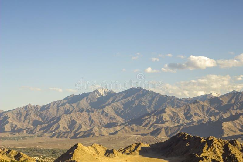 Χιονώδεις αιχμές στα βουνά και το μπλε ουρανό ερήμων στοκ εικόνες