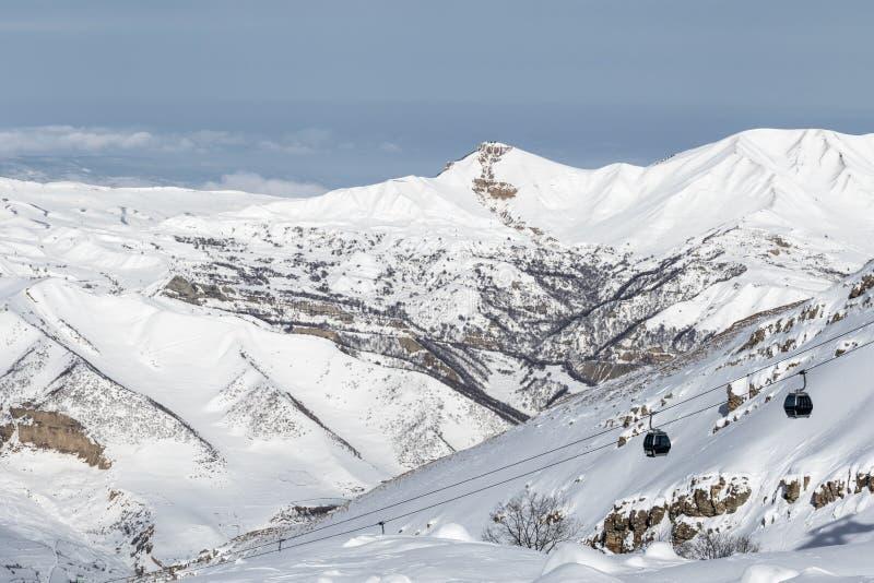 Χιονώδεις βουνά και ανελκυστήρας γονδολών στο χιονοδρομικό κέντρο στην ηλιόλουστη χειμερινή ημέρα στοκ εικόνα με δικαίωμα ελεύθερης χρήσης