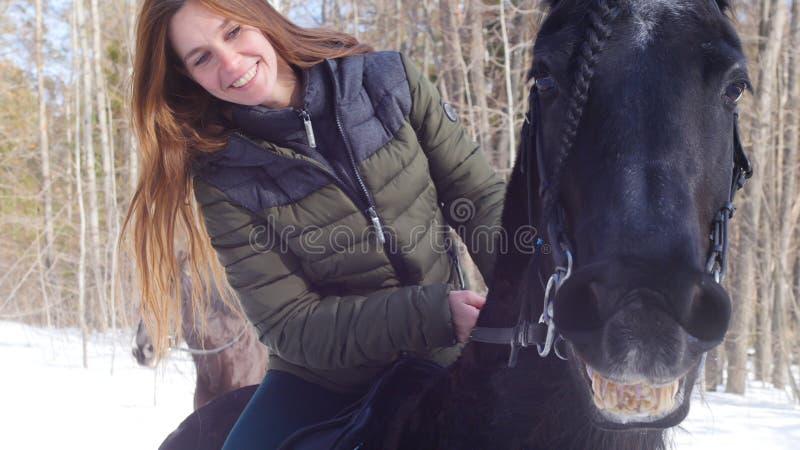 Χιονώδες δάσος στην άνοιξη Χαμογελώντας γυναίκα που οδηγά ένα άλογο χαμόγελου στοκ φωτογραφία με δικαίωμα ελεύθερης χρήσης