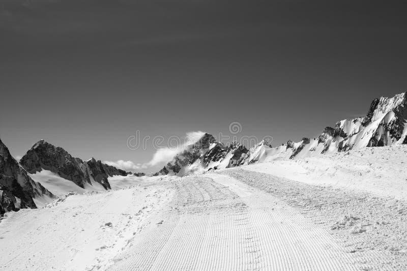 Χιονώδης δρόμος με το ίχνος από το χιόνι groomer και όμορφα χειμερινά βουνά στην κρύα ημέρα ήλιων dombay περιοχή βουνών ημέρας Κα στοκ εικόνες