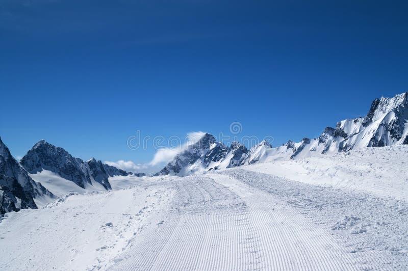 Χιονώδης δρόμος με το ίχνος από το χιόνι groomer και όμορφο χειμερινό mou στοκ εικόνα