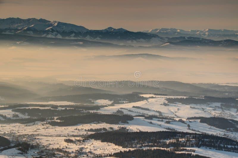 Χιονώδης δυτική άνοδος σειράς Tatras επάνω από τις κοιλάδες στη θάλασσα της ομίχλης στοκ εικόνα