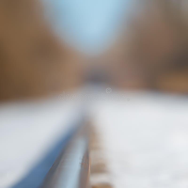 Χιονώδης ευθεία διαδρομή σιδηροδρόμου - χαμηλό βάθος του τομέα και αρκετά θολωμένος bokeh - κοντά στον ποταμό και τον κοντινό μαύ στοκ φωτογραφία