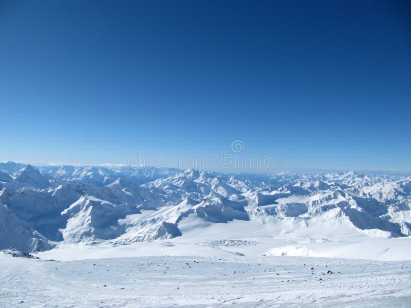 Χιονώδης μεγαλύτερη κορυφογραμμή Καύκασου με την ΑΜ Ushba στη χειμερινή ηλιόλουστη ημέρα Άποψη από Pastuchova kliffs στην κλίση σ στοκ εικόνες