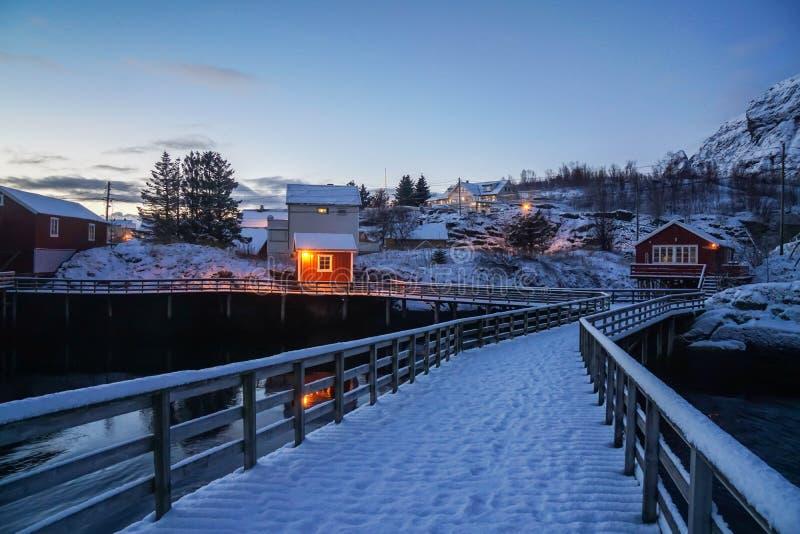 Χιονώδης ξύλινη γέφυρα στα νησιά Lofoten και το κόκκινο ξύλινο σπίτι στο σκηνικό φωτός του ήλιου πρωινού το χειμώνα στοκ φωτογραφία με δικαίωμα ελεύθερης χρήσης
