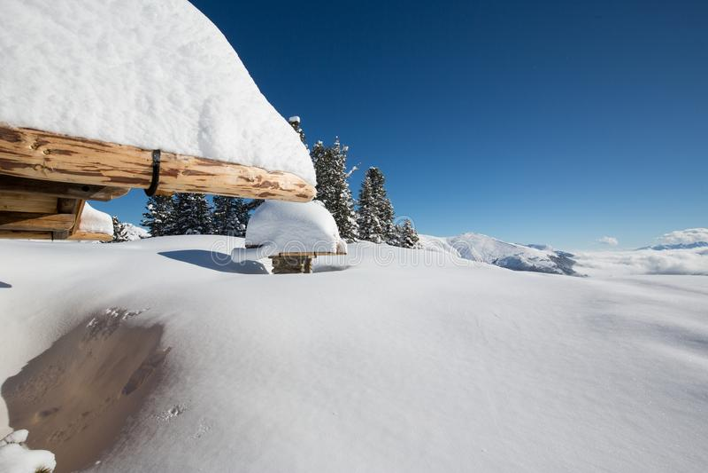 Χιονώδης ξύλινη καλύβα βουνών στις τυρολέζικες Άλπεις στην ηλιοφάνει στοκ εικόνες